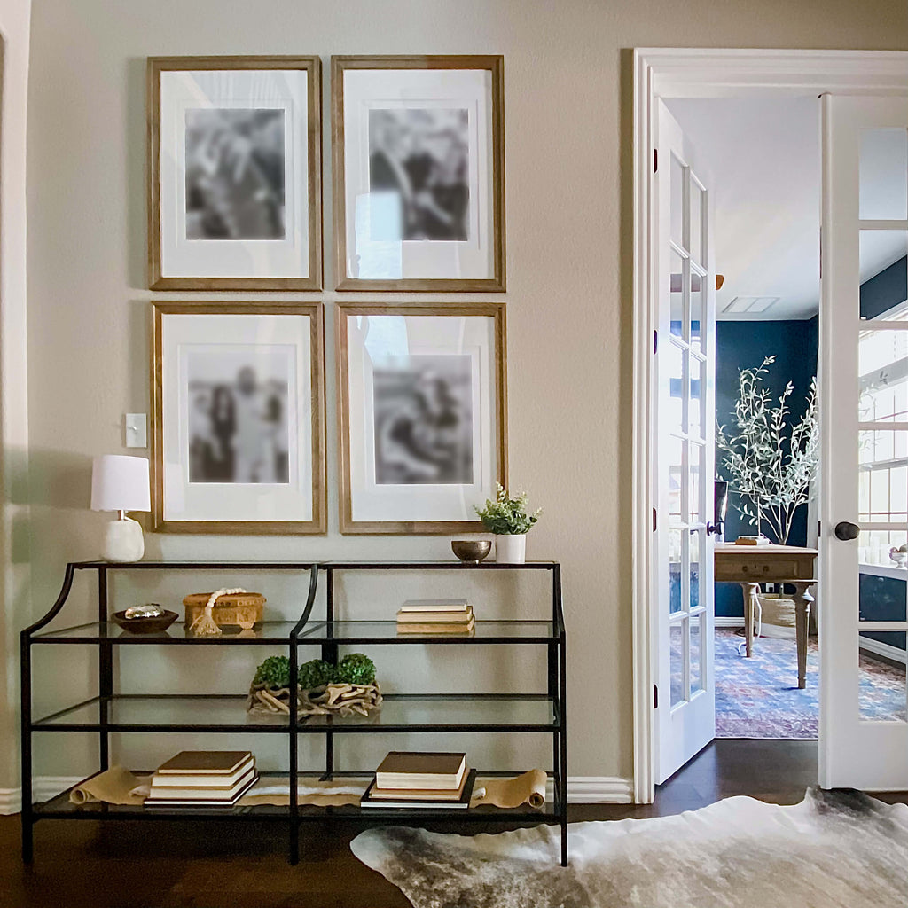 Entryway console with styled natural and functional elements highlighted with four photo framed gallery wall