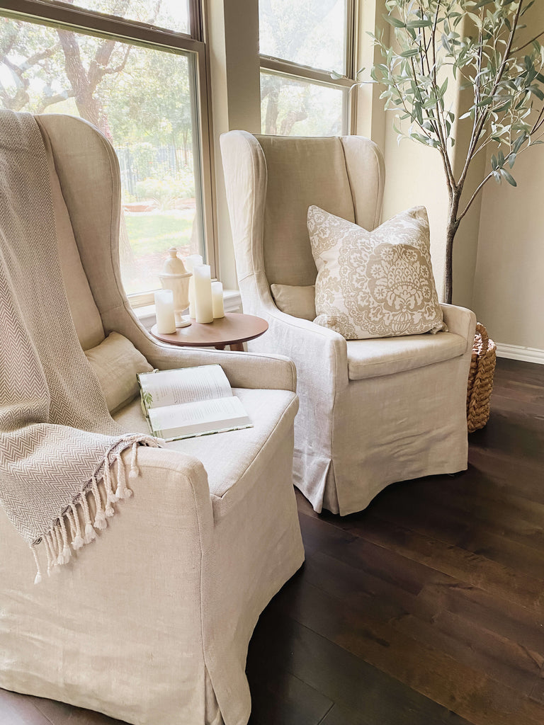 Two linen covered chairs angled together near windows, a cozy blanket draped over one chair with a open book.
