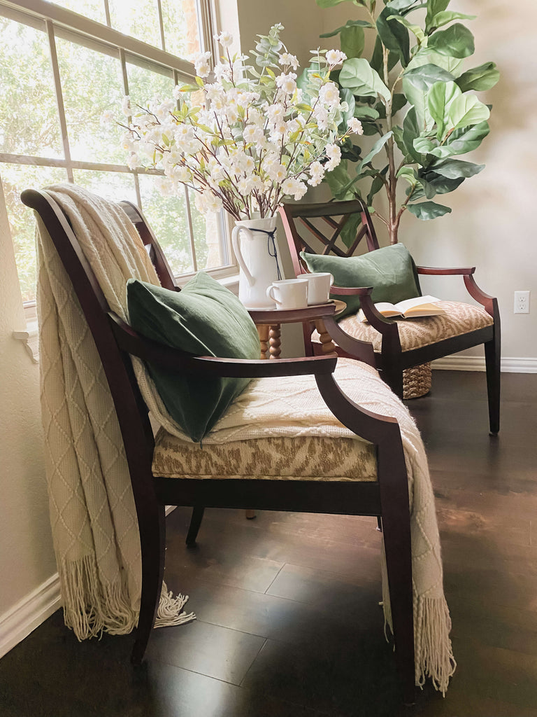 Side view of two chairs near a window with green pillows, a green tree in the background and linen colored blanket draped over the chair