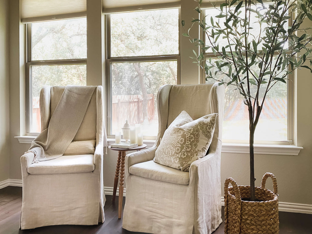 Two linen covered chairs with a small table of candles sit beside an indoor tree with a backdrop of three windows.