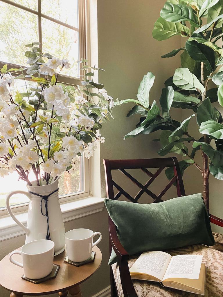 Chair next to window with open book and coffee cups, surrounded by natural light and organics, flowers in a vase plus green leafy tree.
