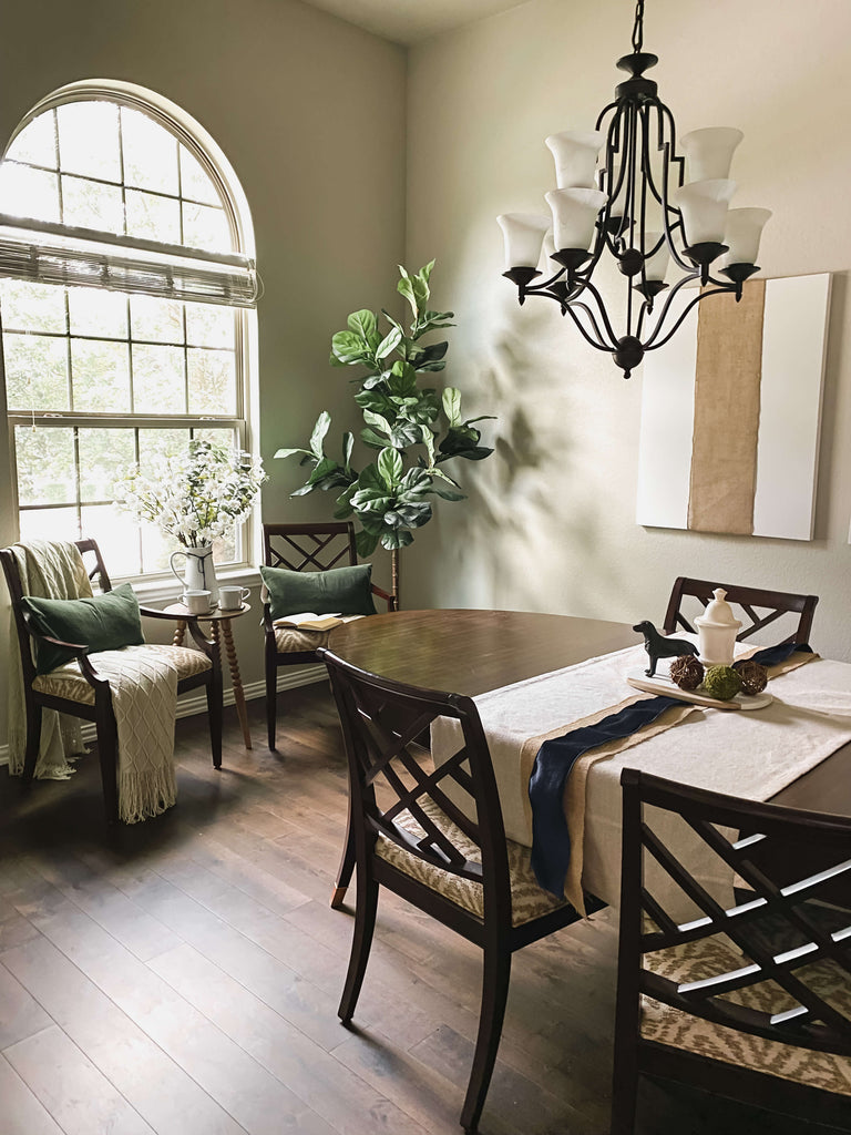 Dining room with neutral decor. Two chairs tucked in by a window for a quite seated moment surrounded by organics