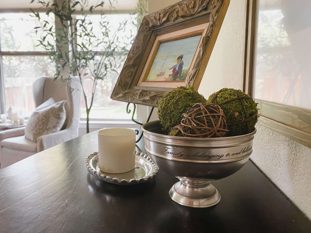 Dresser topped with moss balls in silver bowl, candle and small art framed, decluttered space for calm atmosphere