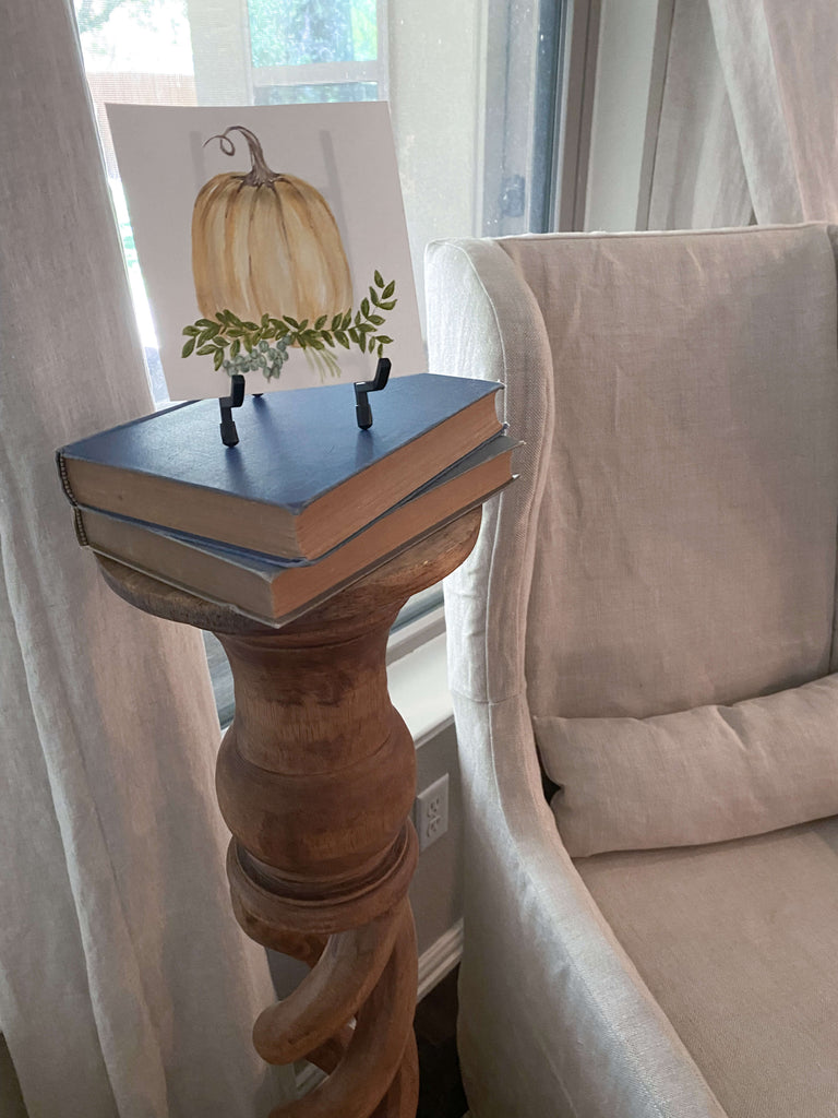 A small watercolor piece of art next to a comfortable chair, a focal point for hosting a small gathering