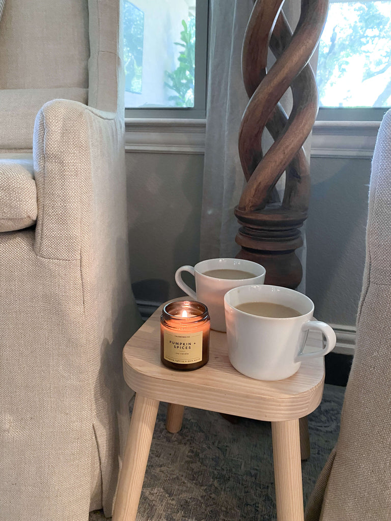 Two coffee cups with a fall candle near two chairs for a cozy, intentional gathering