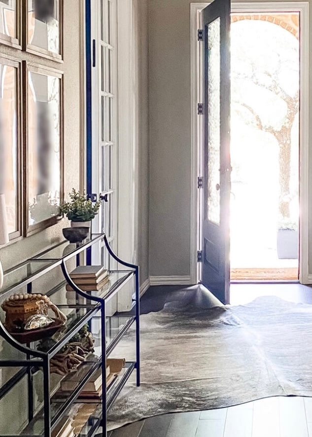 Light shining through open entryway door to an inviting space with a rug and functional console with intentionally designed elements