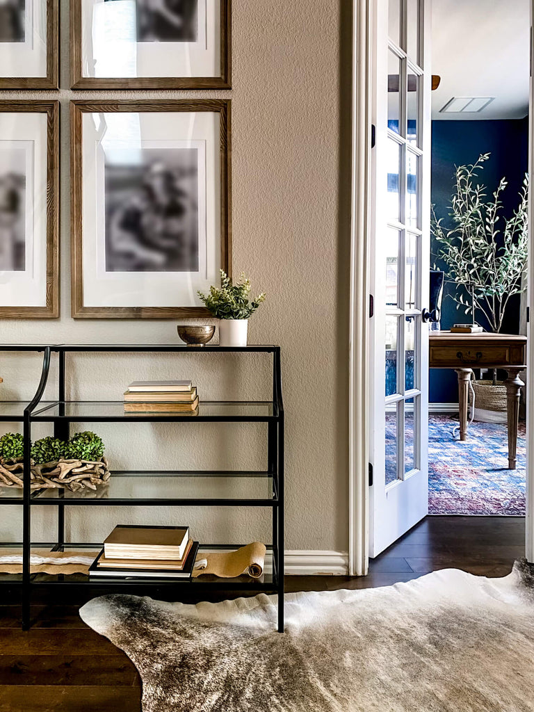 Entryway console with intentionally designed elements like organics, metal bowl and gallery wall