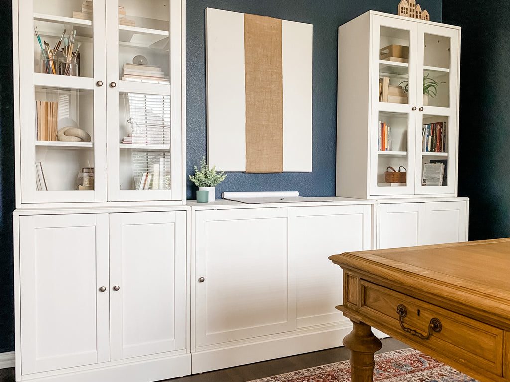 Image of House of Inverness Home Office, viewing the wall units, corner of the desk, and wall decor.