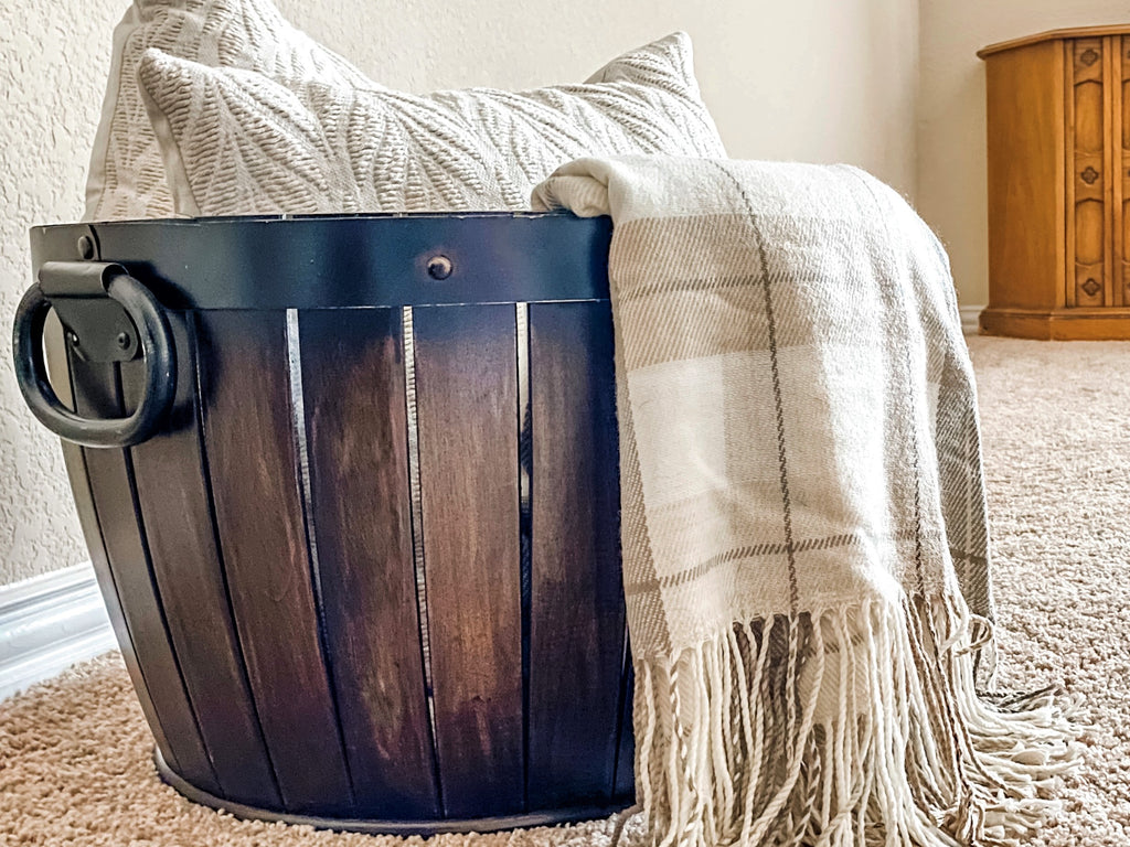Close-up view of a barrel basket containing textured pillows and a fall-themed plaid throw blanket, arranged in House of Inverness' style.