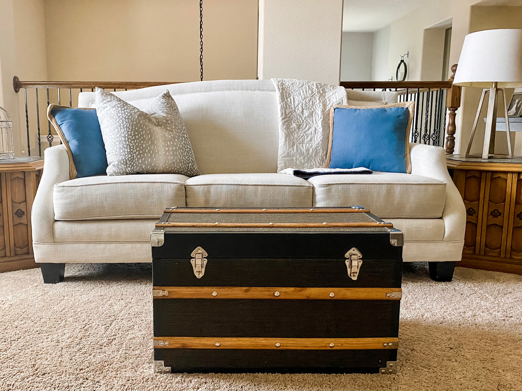 An image of the sofa in the family room, styled still in House of Inverness' summer theme, with simple decor and blue accents.