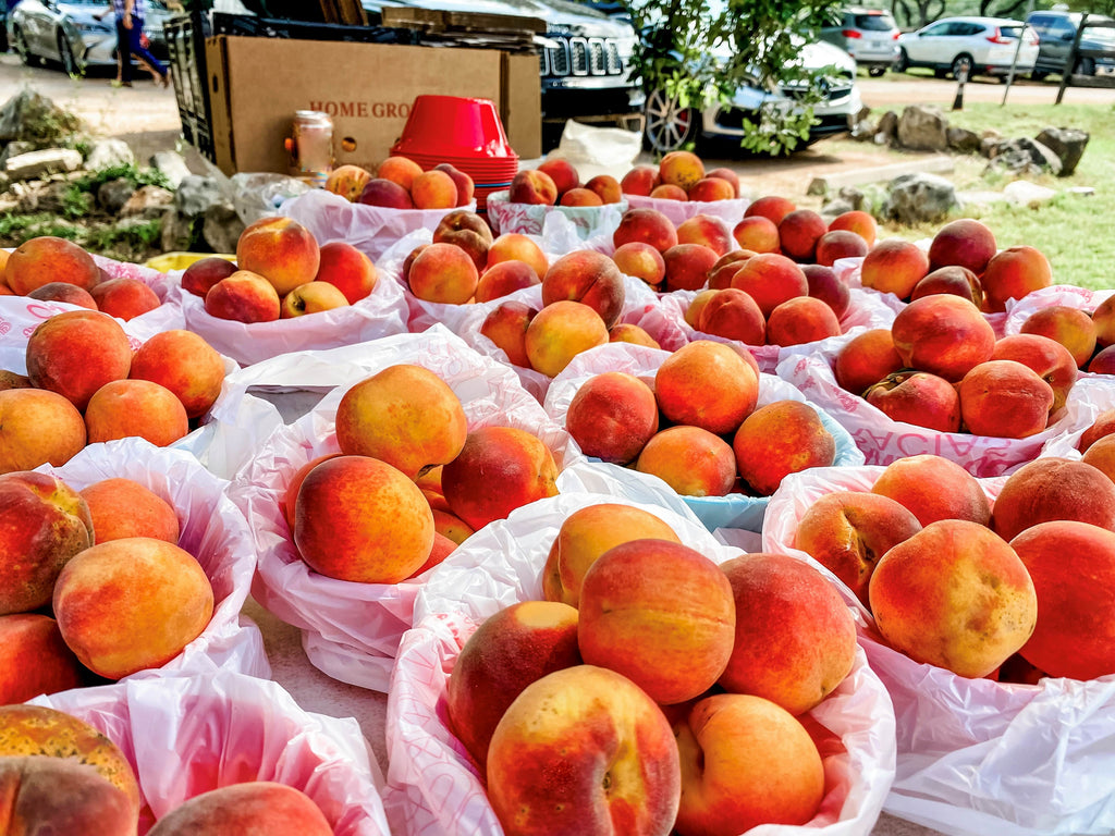 Close-up of a local vendor's table display, featuring fresh and ripe peaches, locally grown.