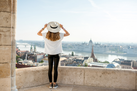 Girl in hat standing in front of city