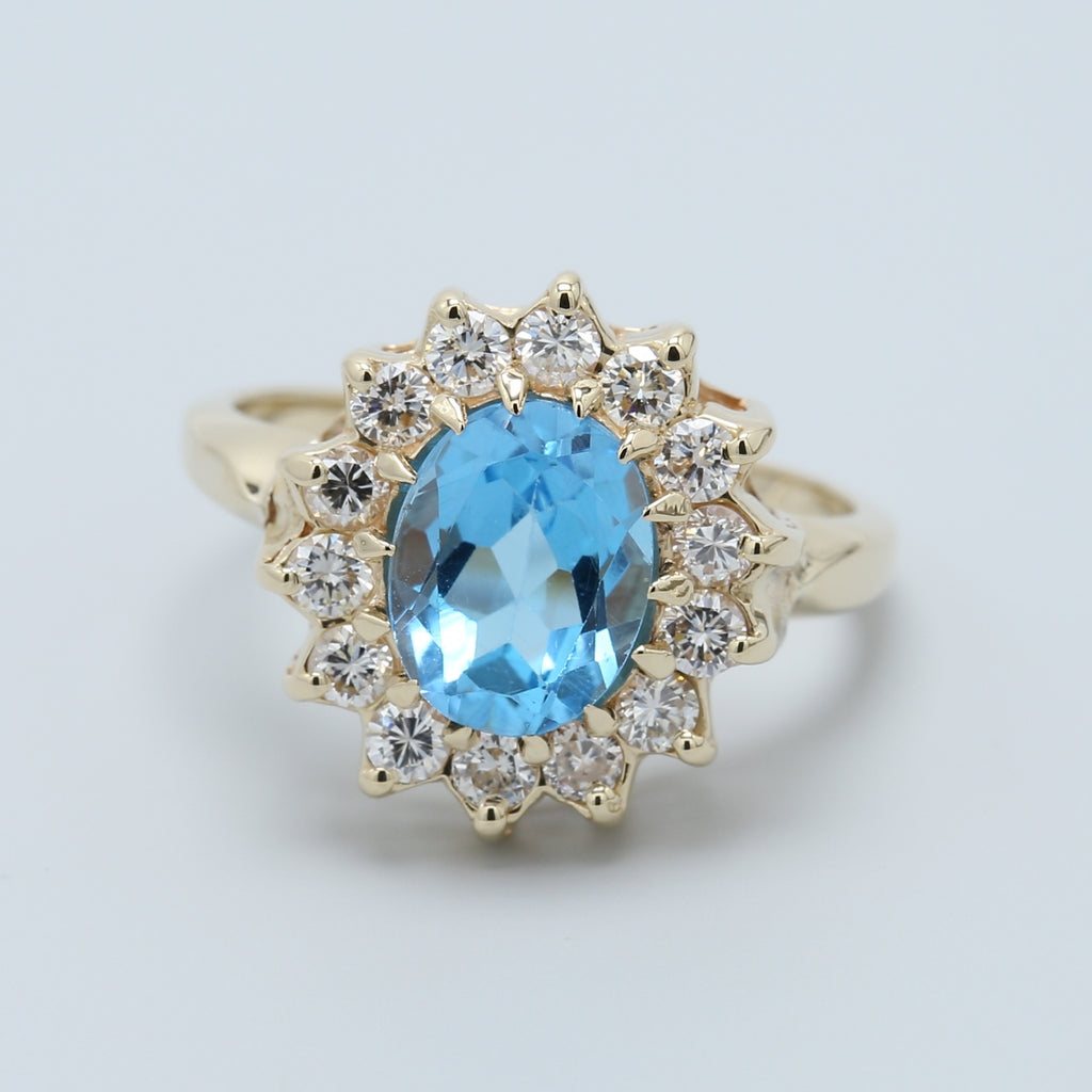 Oval Blue Topaz and Diamond Halo Ring in 14k Yellow Gold - 1477 Jewelers