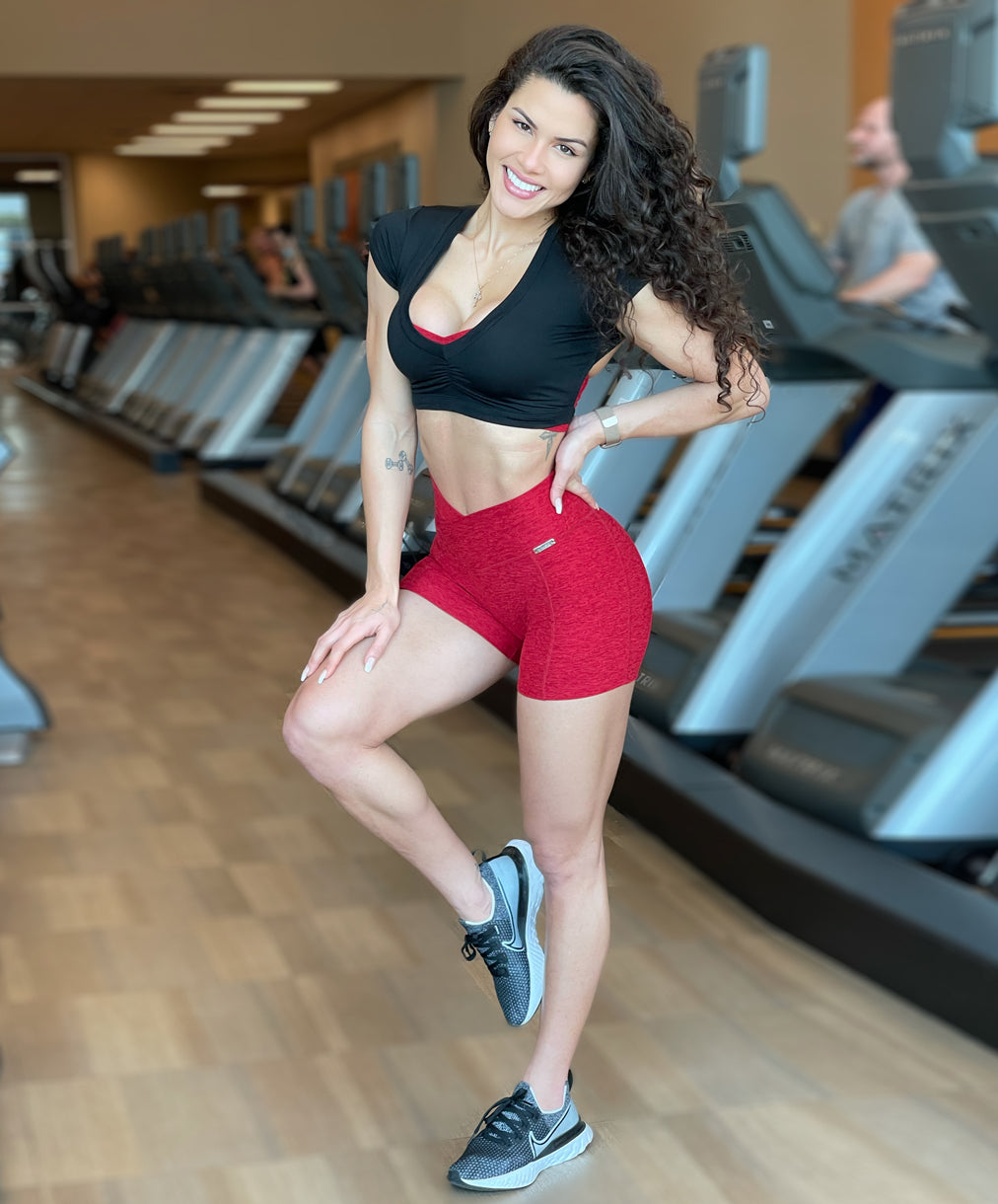 model in red shorts at gym