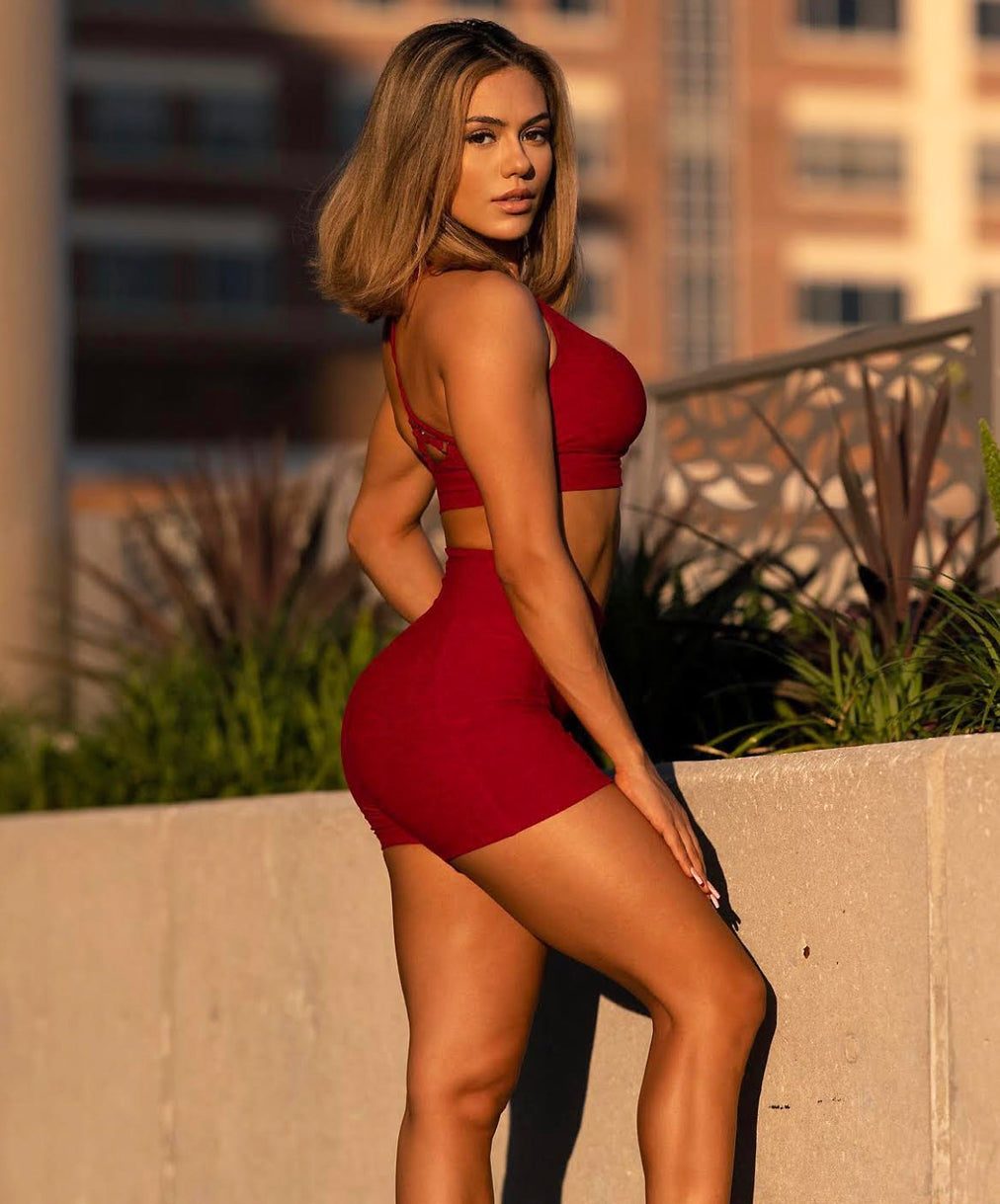 model in red shorts and matching red active top