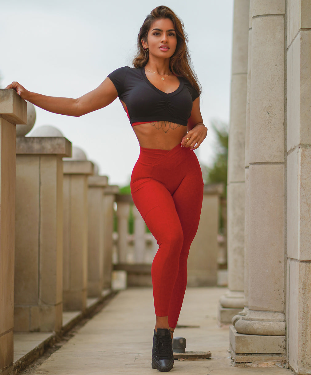 model in black crop top and red workout leggings