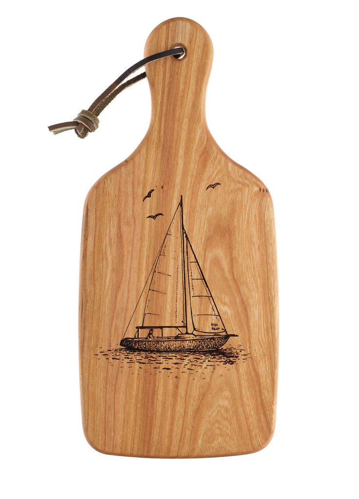 cutting board engraved with a sailboat design