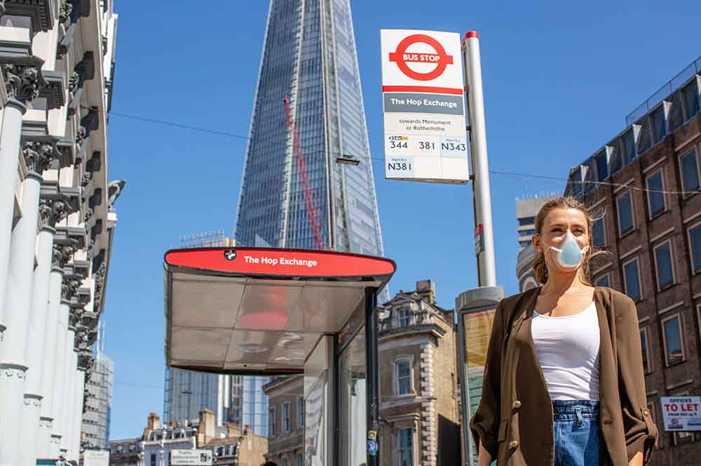 young lady wearing breathe happy commuter face mask next to bus stop in London