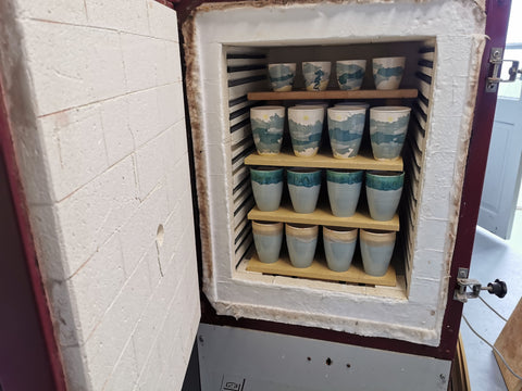 Glaze fired Travel Cups fresh from the kiln atGrounded Pottery