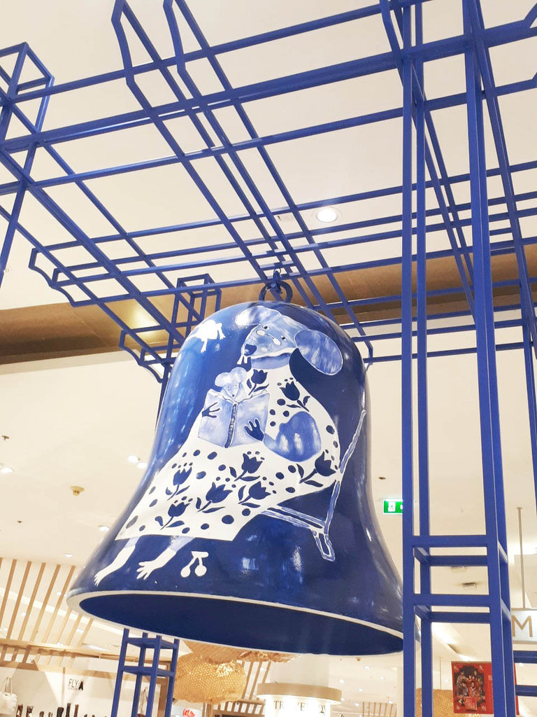 Rat illustration printed onto a large blue bell, suspended from blue railings. Mixed media style by Auracherrybag