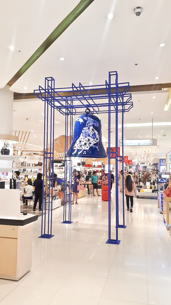 Public installation by mixed media artist Auracherrybag. A blue bell is suspended in a shopping centre, and is printed with an illustration of a white rat. The illustration is in the style of mixed media collage