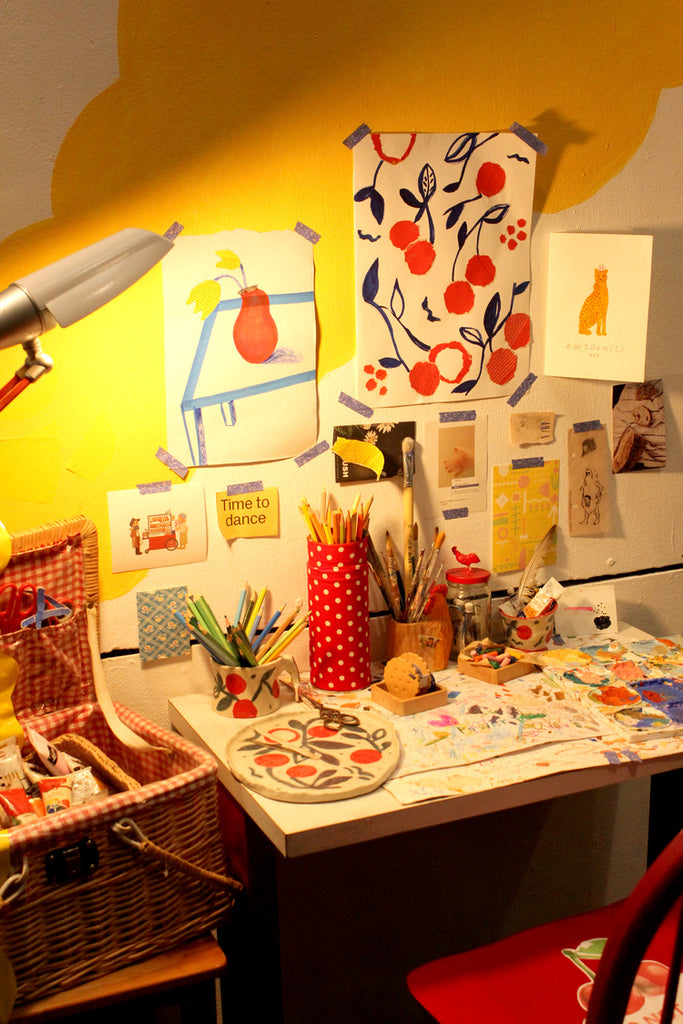 A red chair and a desk covered with working supplies and illustrations at an exhibition by mixed media artist Auracherrybag