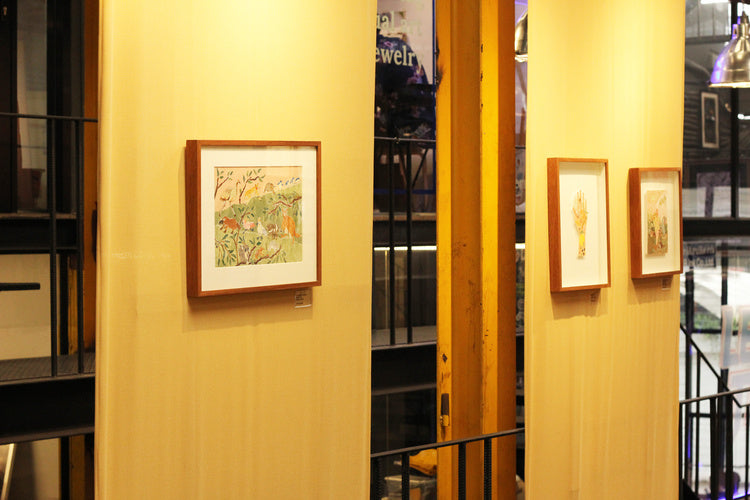 A selection of framed works on a wall from an exhibition by mixed media artist Auracherrybag