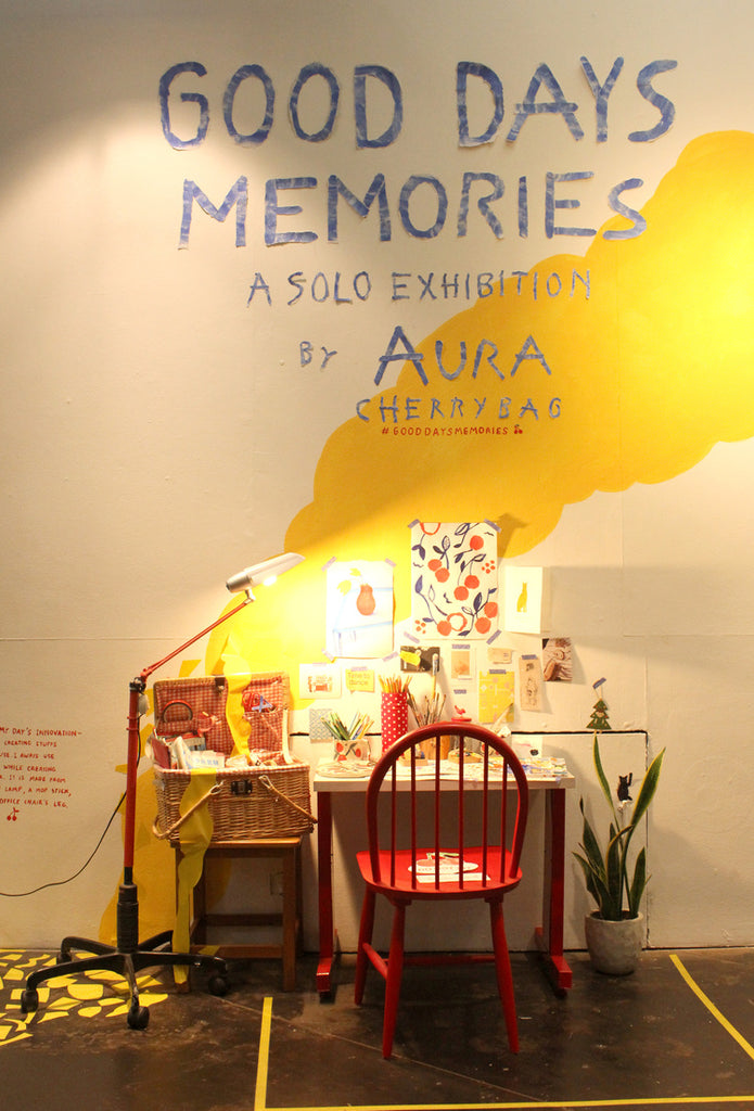A red char and working desk surrounded by illustrations at an exhibition by mixed media artist Auracherrybag