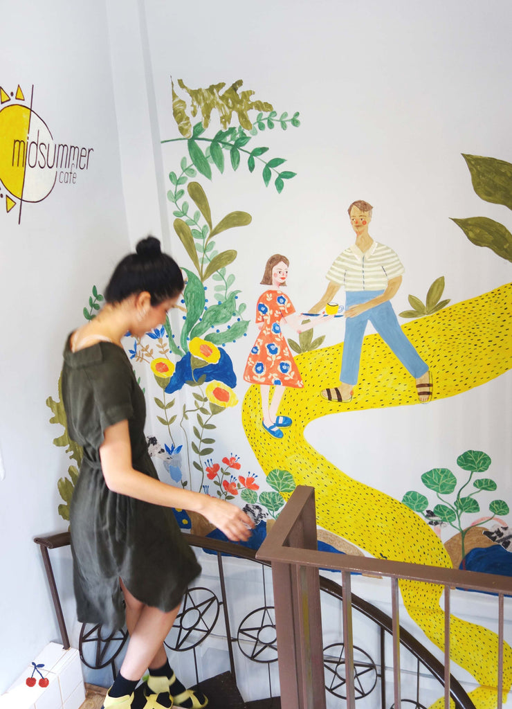 Mixed media artist looking at a mural art piece she created with people walking on a yellow road