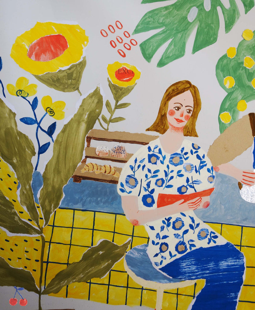 Section of a mural by mixed media artist Auracherrybag that shows a woman in a cafe surrounded by flowers that is reading a book