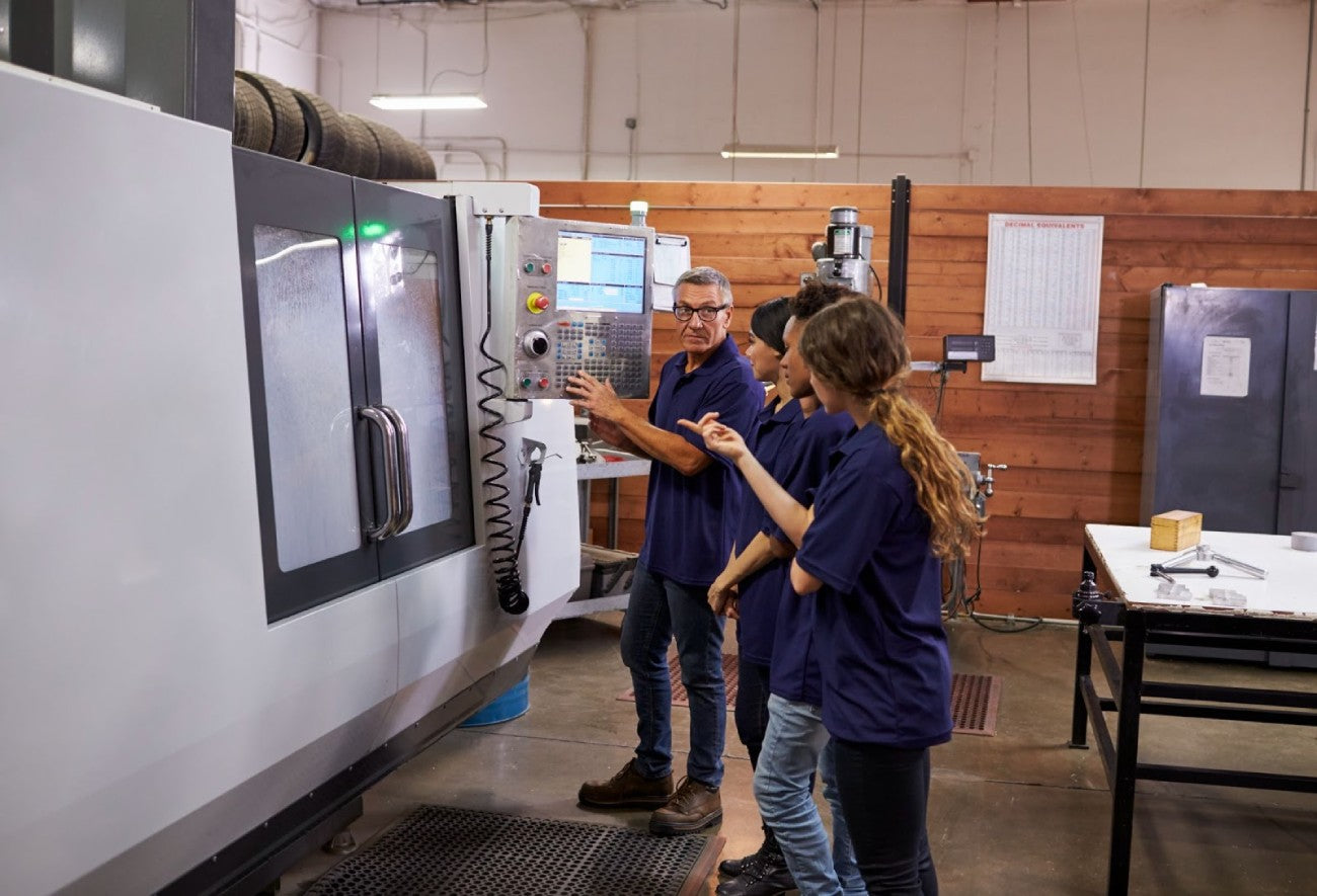 An older man is showing three engineering students how to use a complex machine.
