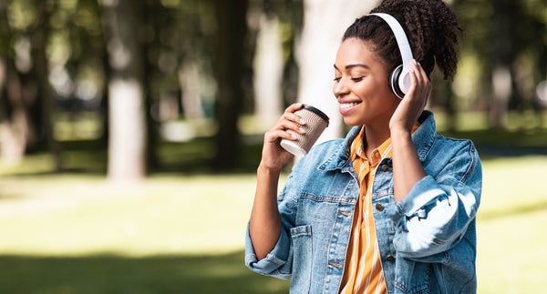 Weekend Concept. African Millennial Girl With Headphones Having Coffee Enjoying Day Walking Outside In Park. Panorama, Copy Space