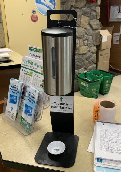 A photo of the brushed steel Triden touchless hand sanitizer dispenser on a table in Thrifty Foods Grocery store..