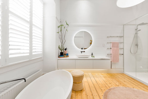 Clean modern bathroom that is well lit. Has a bathtub and shower. The walls are white and there is hardwood flooring.