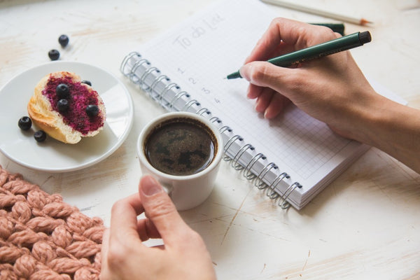 Top view shot of woman sitting at table with coffee writing on notebook. Female making to do list on diary.
