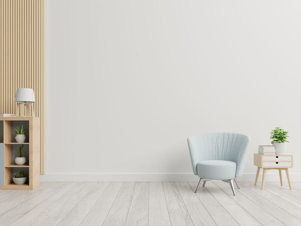 Minimalist room with few decorations and a lot of space in it. Blue chair in right corner and shelving unit in left corner