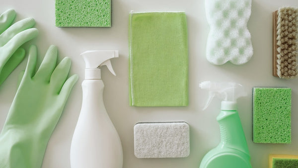 Green protective gloves, sponges,rag, brush, spray cleaner bottle with chemical detergent on white background. Housework and professional eco cleaning service supplies.