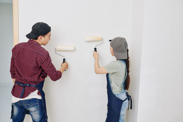 Two people applying matte white paint on wall with paint rollers