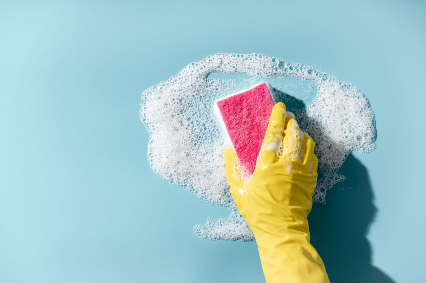 yellow gloved hand is using a soapy pink sponge to clean.