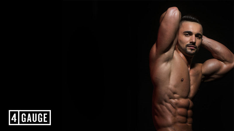 Bodybuilder doing an abs pose on a black background