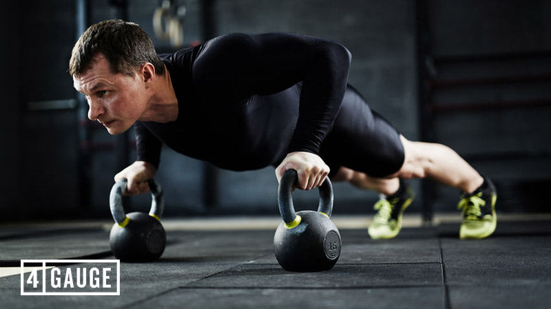 Man doing pressups on kettlebells in the gym
