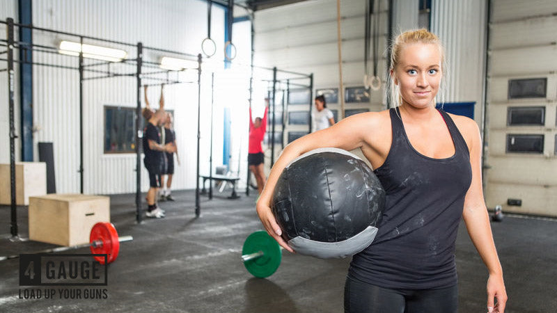 Woman in CrossFit gym holding a medicine ball