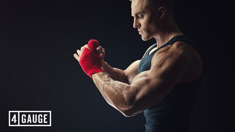 Male athlete wrapping hands and getting a muscle pump