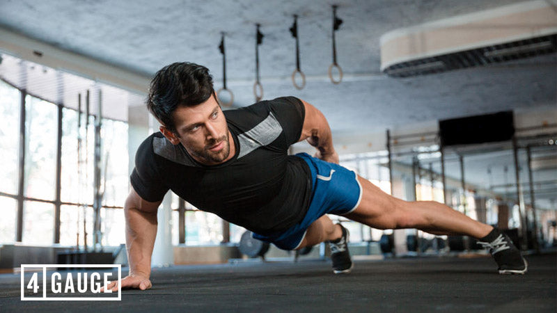 Athletic man doing one-handed push-ups in the gym
