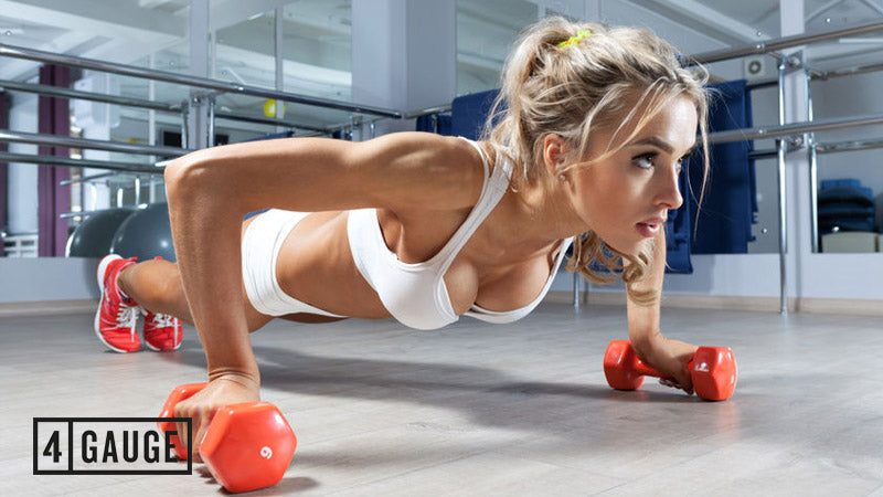 Sporty female doing press ups in the gym on dumbbells