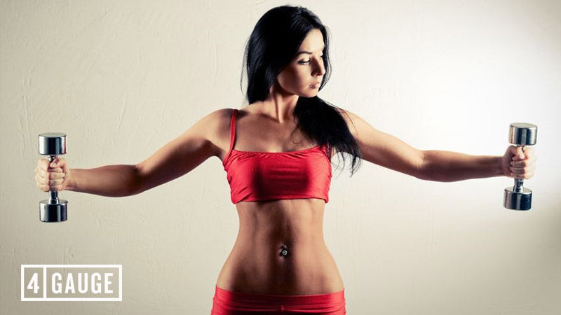 Dark-haired woman in a red sports top and pants doing a lateral raise with dumbbells