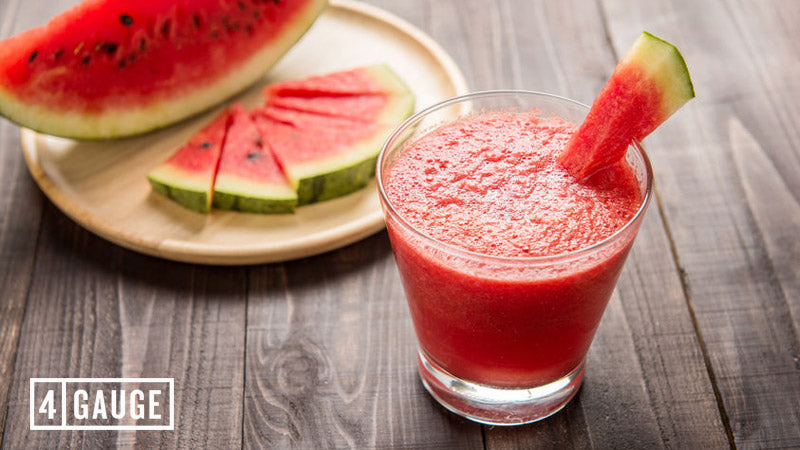 A glass of watermelon juice high in citrulline malate on a wooden table. There are slices of watermelon in the background on a plate
