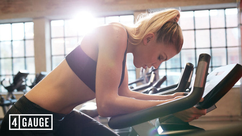 Blonde-haired woman in sportswear cycling in the gym