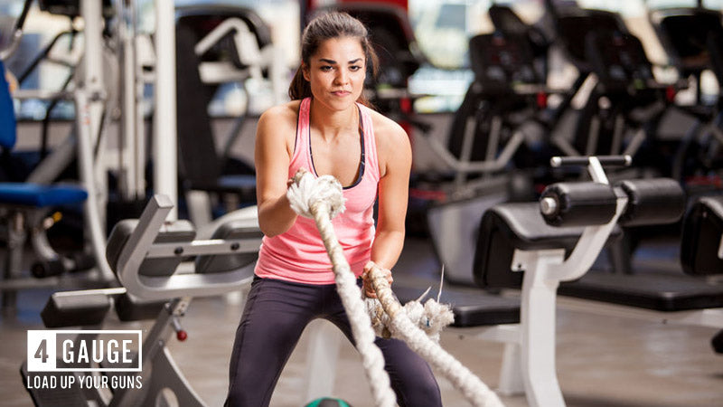 Young, fit woman in the gym working out with battle ropes