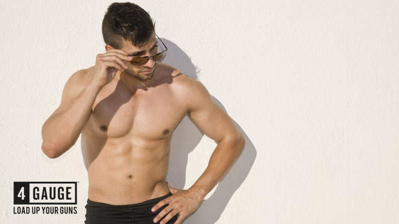 Athletic, muscular man in sunglasses with six pack abs